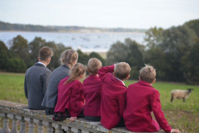 pupils from Ipswich High School sit on a wall at the campus and overlook the River Orwell