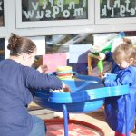A toddler playing with sand at Ipswich High School's Parent and Toddler group