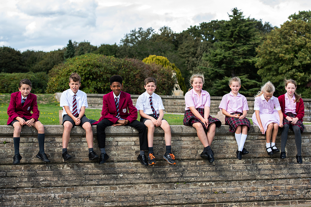School children sat on a brick wall